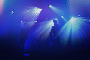 Rock band silhouettes on stage.