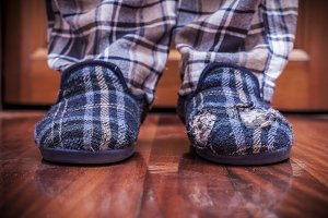 Man feet at home with broken slipper
