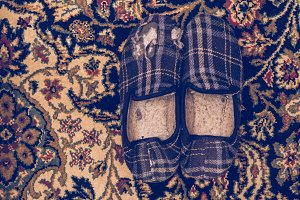 Broken winter slippers on a carpet