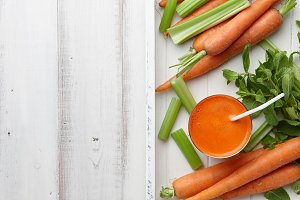 Fresh carrot and celery juice in wooden tray