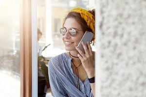 Young businesswoman wearing sunglasses and casual shirt staying at home looking out of window communicating over cell phone having good mood and pleasant smile enjoying sunny weather and having rest