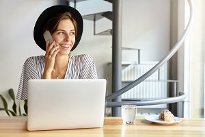 Attractive businesswoman wearing blak summer hat having graceful and happy look while speaking over smartphone with her lover working at white modern laptop. People, technology, lifestyle concept