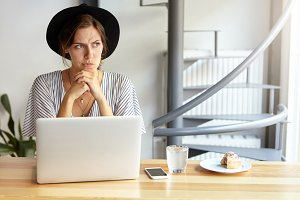 Indoor shot of attractive young woman looking elegantly while wearing black hat and stripped blouse sitting at wooden table in front of laptop having dreams. Woman with thoughtful expression