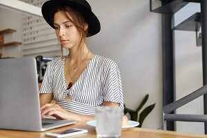 Portrait of elegant lady wearing black hat and blouse sitting in office in front of opened laptop working. Successful female blogger writing new post, sitting at wooden table with her computer
