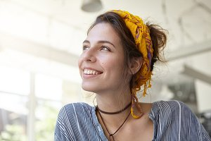 Style, fashion and clothing concept. Trendy woman having yellow scarf on head and wearing stripped shirt having carefree expression looking up. Positive hipster woman isolated over white walls