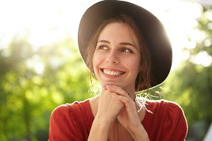 Outdoor portrait of gorgeous woman with healthy look wearing black hat and red shirt holding hands under chin looking with sincere smile aside isolated over green nature background. Vacations concept