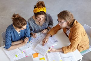 Bearded hipster guy in glasses sitting near his two female groupmates showing them something in book pointing with finger at main passage trying to explain something. Three people working togehter