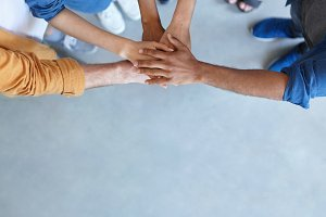 Friendship, partnership, togetherness, collaboration concept. Group of international friends stacking their hands expressing their friendship, agreement and support. People piling their hands