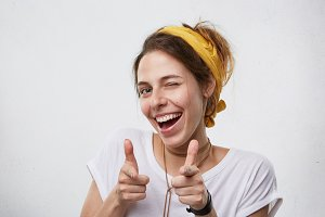 Positive cheerful young woman wearing yellow scarf on head and white casual T-shirt blinking her eyes and smiling pointing at camera with index fingers. Happy attractive woman pointing at you
