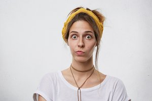 Headshot of cute female staring at camera wearing white T-shirt and yellow headband curving her lips isolated over white studio background. Shocked woman in casual clothes hearing awful news on TV
