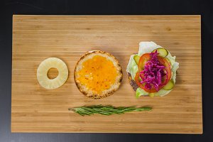 Open burger with pineapple on wooden board