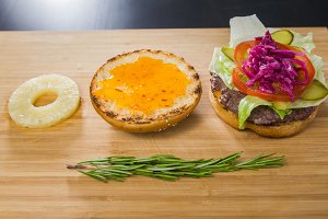 Open burger with pineapple and red onion on wooden board