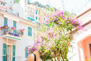 Beautiful happy woman having fun during holidays in Cinque Terre. Young caucasian tourist walking at the old street