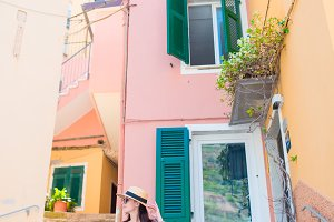 Beautiful happy woman during european holidays in Cinque Terre. Young caucasian tourist walking at the old street