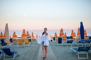 Young woman enjoying summer day on the beach in the sunset. Beach vacation in Europe