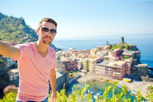 Happy young man taking selfie background the old coastal town of Vernazza, Cinque Terre National Park, Italy