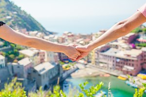 Closeup hands of couple with view of the old coastal town background of Vernazza, Cinque Terre national park, Liguria