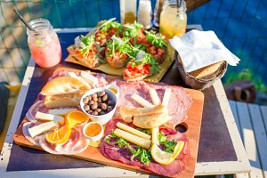 Tasty italian food. Fresh bruschettes, cheeses and meat on the board in outdoor cafe with amazing view in Manarola, Italy