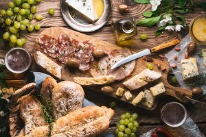Homemade bread, cheese, olives, grapes, flowers on old boards