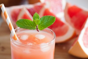 Freshly pressed grapefruit juice with mint leaves and ice on white table close up