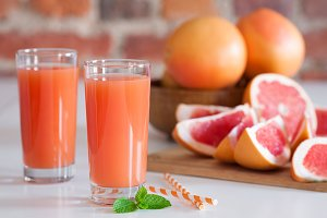 Freshly pressed grapefruit juice with mint leaves on brick wall background closeup