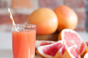 Freshly pressed grapefruit juice with mint leaves and ice on the brick wall background closeup