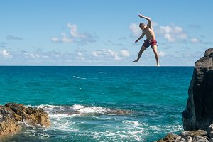 Fit young man jumps into ocean at Lumahai beach Kauai