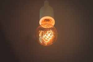Old electric lightbulb in darkness