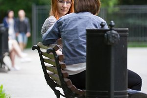 A girl in glasses sits on a bench next to a girlfriend