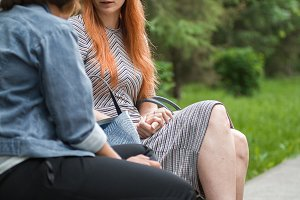 Two women friends talk to each other, sitting on a bench