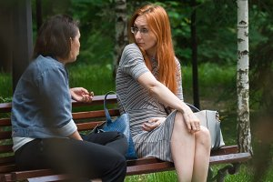 The girl looks at her friend in surprise, sitting on a bench