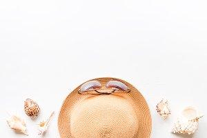sunglasses, straw hat and seashells