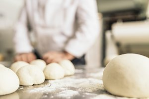 Baker making bread at a bakery.