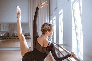 The young modern ballet dancer posing against the room background