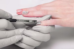 Closeup finger nail care by manicure specialist in beauty salon.