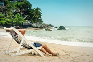 Young man relax in beach chair and enjoy seascape on tropical beach