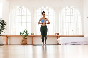Fit young woman meditating indoors