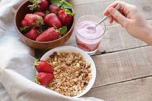 Healthy breakfast. Muesli and yogurt with strawberries. A woman's hand puts a spoonful of yogurt in the muesli