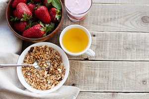 A bowl of homemade granola with yogurt and fresh strawberries on a wooden background. Healthy breakfast with green tea
