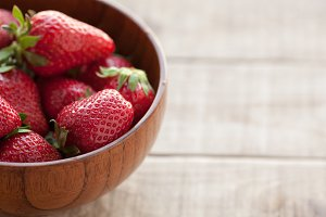 Fresh strawberries in a wooden bowl on a wooden table.