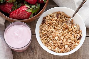 A bowl of homemade granola with yogurt and fresh strawberries on a wooden background. Healthy breakfast