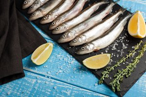 Fresh sea fish smelt or sardines ready for cooking with lemon, thyme, and coarse sea salt on a blue background. The concept of fresh, healthy seafood. Top view