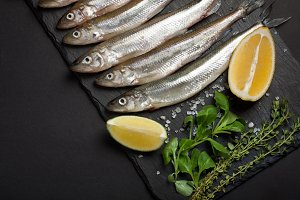Fresh sea fish smelt or sardines ready for cooking with lemon, thyme, and coarse sea salt on a black background. The concept of fresh, healthy seafood. Top view