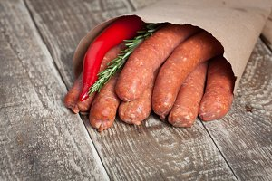 Raw homemade sausages of lamb with rosemary and chili pepper in a paper envelope on a black wooden Board