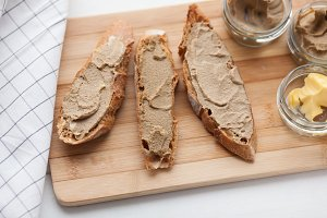Bread with veal and rabbit pate with butter on a bamboo board