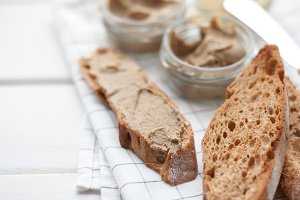 Bread with veal and rabbit pate with butter on a textile background