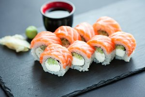 Philadelphia roll classic dark stone on the Board. Salmon, Philadelphia cheese, cucumber, avocado. Japanese sushi.