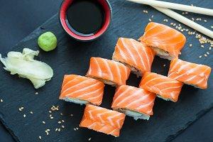 Philadelphia roll classic on a dark stone background. Philadelphia cheese, cucumber, avocado. Japanese sushi. Top view
