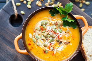 Homemade pumpkin soup with cream, bread, greens and pumpkin seeds on a wooden background. Top viev