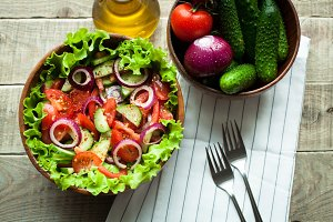 Rustic salad of fresh tomatoes, cucumbers, red onions and lettuce, dressed with olive oil and ground pepper in a wooden bowl. Top view